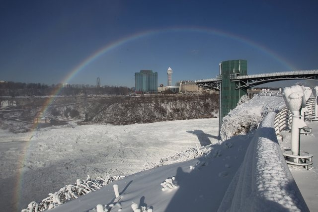 The mist from Niagara Falls creates a rainbow on Propect Point in Niagara Falls State Park, Niagara Falls, N.Y. on Thursday, Jan. 9, 2014.  Niagara Falls hasn't frozen over, but it has become an i ...