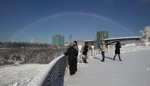 The mist from Niagara Falls creates a rainbow for tourists on Propect Point in Niagara Falls State Park, Niagara Falls, N.Y. on Thursday, Jan. 9, 2014. Niagara Falls hasn't frozen over, but it has ...