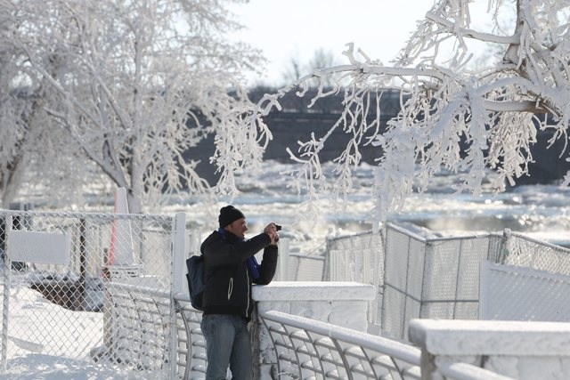 A tourist takes a photograph of the ice created by freezing mist from Niagara Falls in Niagara Falls State Park, Niagara Falls, N.Y. on Thursday, Jan. 9, 2014.  Niagara Falls hasn't frozen over, b ...
