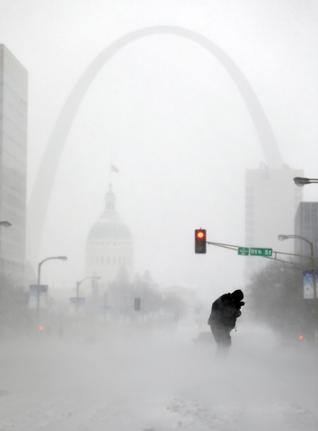 A person struggles to cross a street in blowing and falling snow as the Gateway Arch appears in the distance, in St. Louis. The deep freeze that gripped much of the nation this week wasn't unprece ...