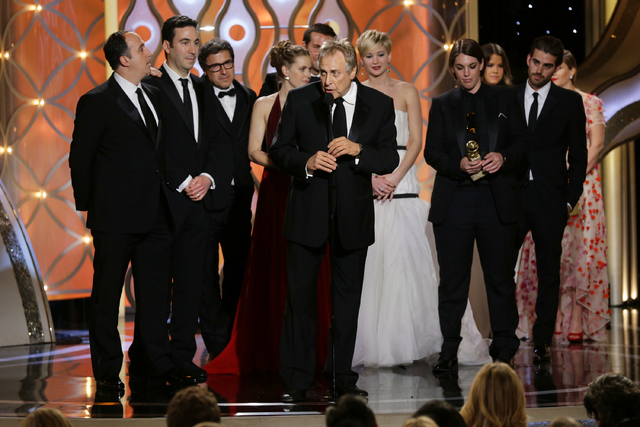"""Charles Roven, center, accepts the award for best motion picture comedy for """"American Hustle"""" during the 71st annual Golden Globe Awards on Sunday. (AP Photo/NBC, Paul Drinkwater)"""