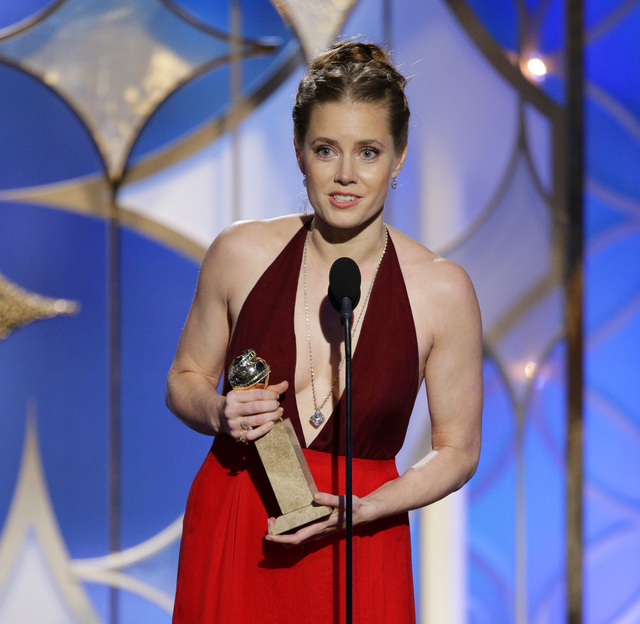 """Amy Adams accepts the award for best actress in a motion picture, musical or comedy for her role in, """"American Hustle"""" during the 71st annual Golden Globe Awards on Sunday. (AP Photo/NBC, Paul Dri ..."""