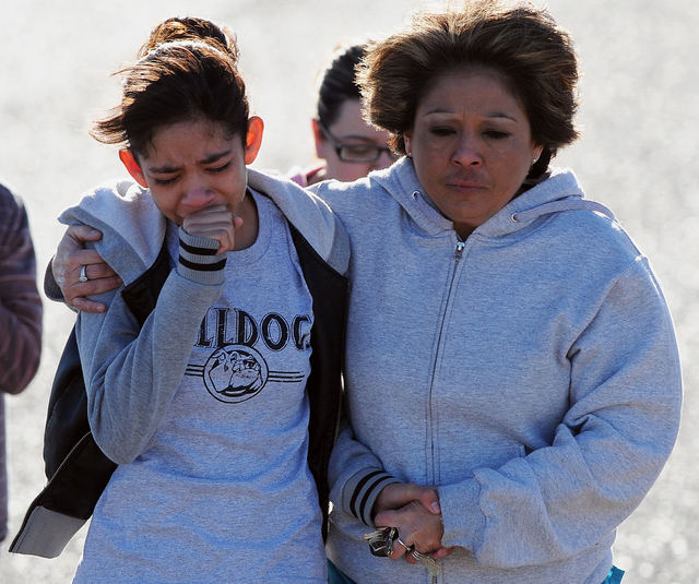 A student, left, is hugged following a shooting at Berrendo Middle School, Tuesday, Jan. 14, 2014, in Roswell, N.M. A shooter opened fire at the middle school, injuring at least two students befor ...