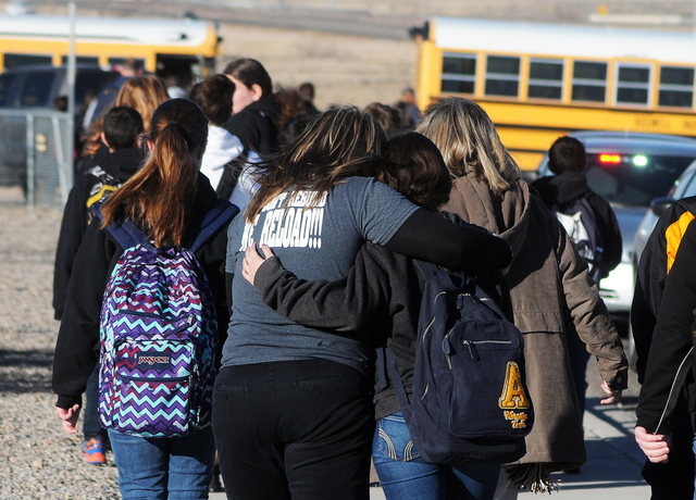 Students are escorted from Berrendo Middle School after a shooting incident, Tuesday, Jan. 14, 2014, in Roswell, N.M. Roswell police said the suspected shooter was arrested at the school, but auth ...