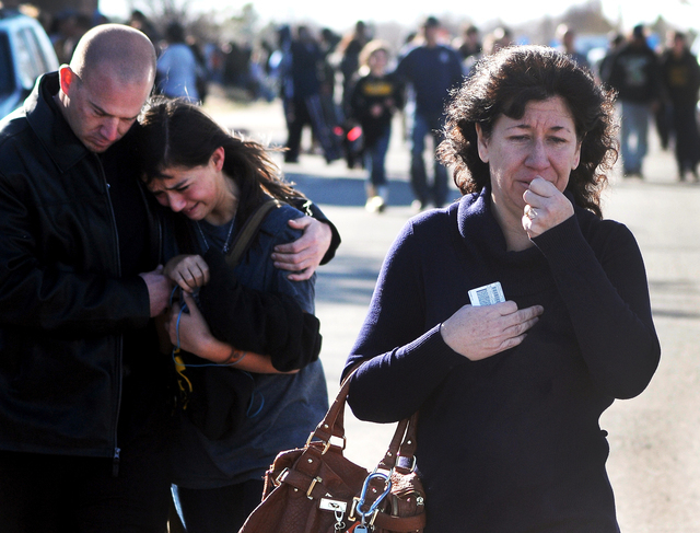 A woman waits at a staging ground area where families are being reunited with Berrendo Middle School students after a shooting at the school, Tuesday, Jan. 14, 2014, in Roswell, N.M. A shooter ope ...