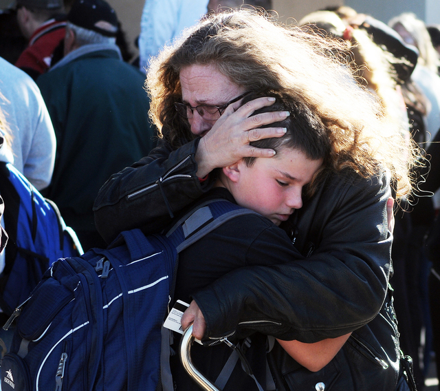 A woman hugs a student at a staging ground set up at the Roswell Mall following a shooting at Berrendo Middle School, Tuesday, Jan. 14, 2014, in Roswell, N.M. A shooter opened fire at the middle s ...