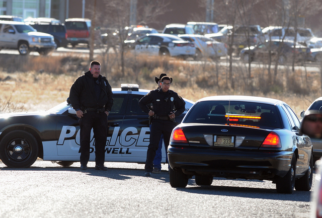 Law enforcement personnel set up a perimeter following a shooting at Berrendo Middle School in Roswell, Tuesday, Jan. 14, 2014, in Roswell, N.M. A shooter opened fire at the middle school, injurin ...