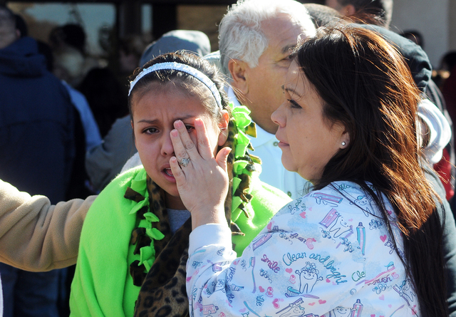 A woman wipes a girl's eyes at a staging ground area set up at the Roswell Mall, where families were united after a shooting at Berrendo Middle School, Tuesday, Jan. 14, 2014, in Roswell, N.M. A s ...