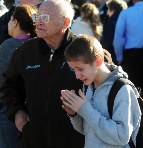A student, right, waits at a staging ground area set up at the Roswell Mall following a shooting at Berrendo Middle School, Tuesday, Jan. 14, 2014, in Roswell, N.M. A shooter opened fire at the mi ...