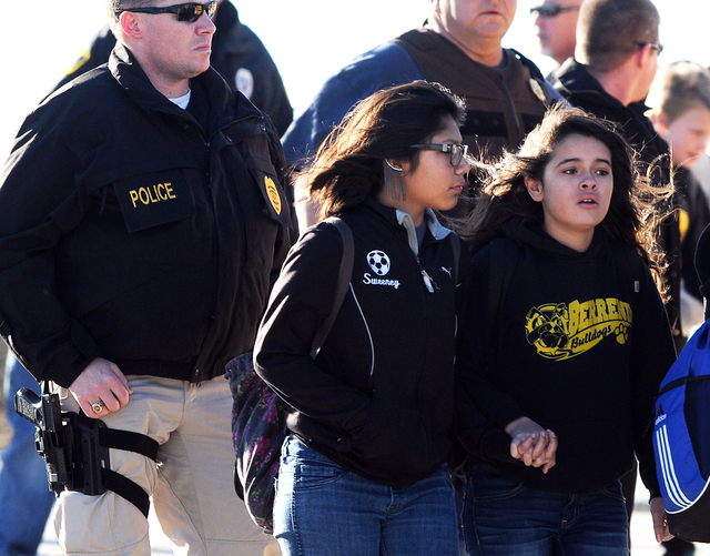 Students surrounded by officials are escorted from Berrendo Middle School after a shooting, Tuesday, Jan. 14, 2014, in Roswell, N.M. Roswell police said the suspected shooter was arrested at the s ...
