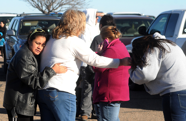 People wait for news at a staging ground area set up at the Roswell Mall after a shooting at Berrendo Middle School, Tuesday, Jan. 14, 2014, in Roswell, N.M. A shooter opened fire at the middle sc ...