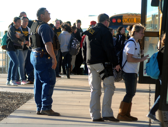 Authorities stand guard as students are escorted from Berrendo Middle School after a shooting, Tuesday, Jan. 14, 2014, in Roswell, N.M. A shooter opened fire at the middle school, injuring at leas ...