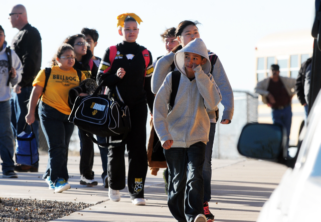 Students are escorted from Berrendo Middle School after a shooting, Tuesday, Jan. 14, 2014, in Roswell, N.M. A shooter opened fire at the middle school, injuring at least two students before being ...