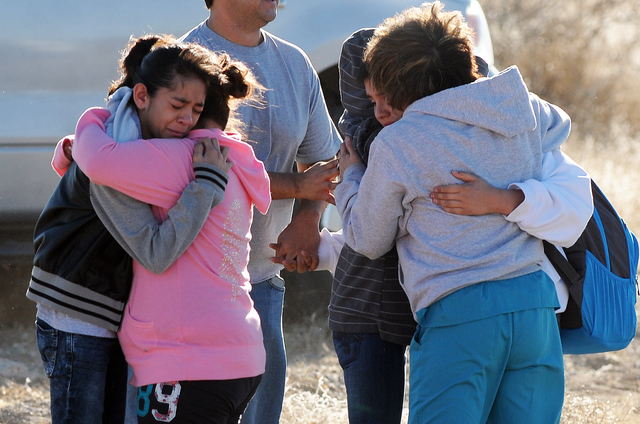 Students are reunited with family following a shooting at Berrendo Middle School, Tuesday, Jan. 14, 2014, in Roswell, N.M. Roswell police said the suspected shooter was arrested at the school, but ...