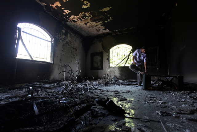This Sept 13, 2012 file photo shows a Libyan man investigating the inside of the  U.S. Consulate in Benghazi, Libya, after an attack that killed four Americans, including Ambassador Chris Stevens. ...