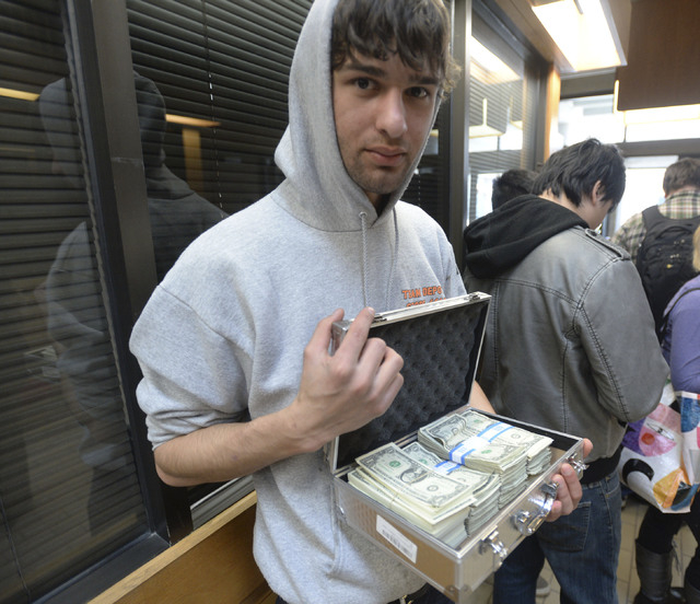 University of Utah student Luke Mughal holds a briefcase full of one-dollar bills as he waits in a long line to pay his tuition at the Student Services Building on the University of Utah campus in ...