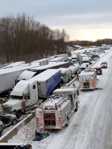 In this photo provided by the Indiana State Police, emergency crews work at the scene of a massive pileup involving about 15 semitrailers and about 15 passenger vehicles and pickup trucks along In ...