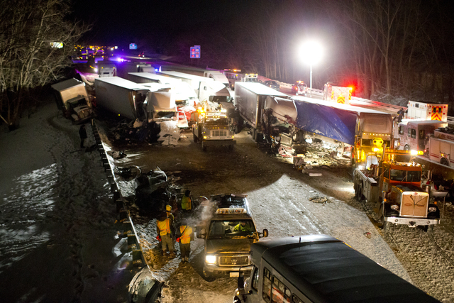 UPDATES CAPTION - Emergency crews work at the scene of a massive pileup involving more than 40 vehicles along Interstate 94 Thursday, Jan. 23, 2014 near Michigan City, Ind. Authorities say a coupl ...