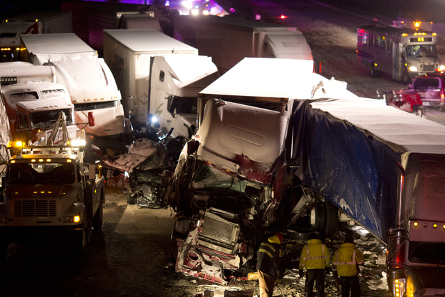 Emergency crews work at the scene of a massive pileup involving about 15 semitrailers and about 15 passenger vehicles and pickup trucks along Interstate 94 Thursday afternoon, Jan. 23, 2014 near M ...