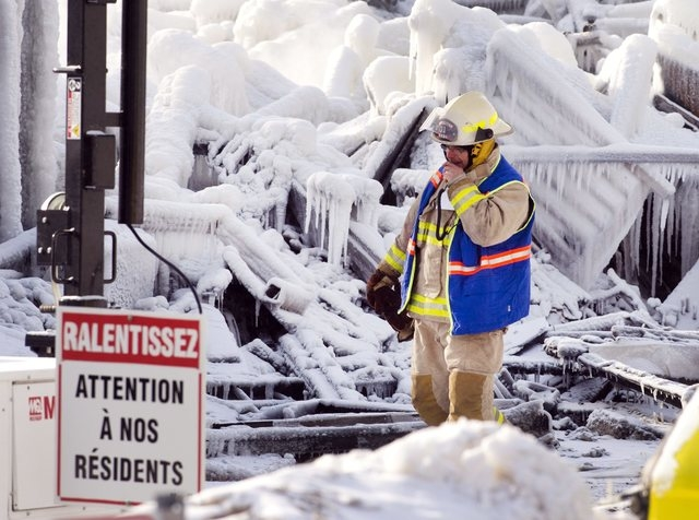 """An emergency worker walks past a sign that reads """"Look out for our residents"""" as they search through the icy rubble of a fire that destroyed a seniors' residence Friday, Jan. 24, 2014, i ..."""