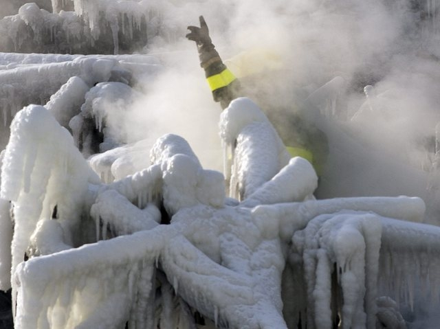 A police investigator, enveloped in steam, signals to colleagues as they search through the icy rubble of a fire that destroyed a seniors' residence Friday, Jan. 24, 2014, in L'Isle-Verte, Quebec. ...