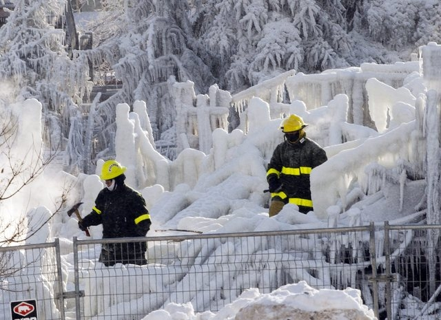 Rescue personnel search through the icy rubble of fire that destroyed a seniors' residence Friday, Jan. 24, 2014, in L'Isle-Verte, Quebec. Five people are confirmed dead and 30 people are still mi ...