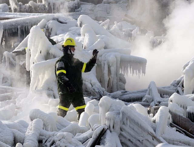 A police investigator signals to colleagues as they search through icy rubble to trying to locate more victims of a fire that destroyed a seniors' residence Friday, Jan. 24, 2014, in L'Isle-Verte, ...