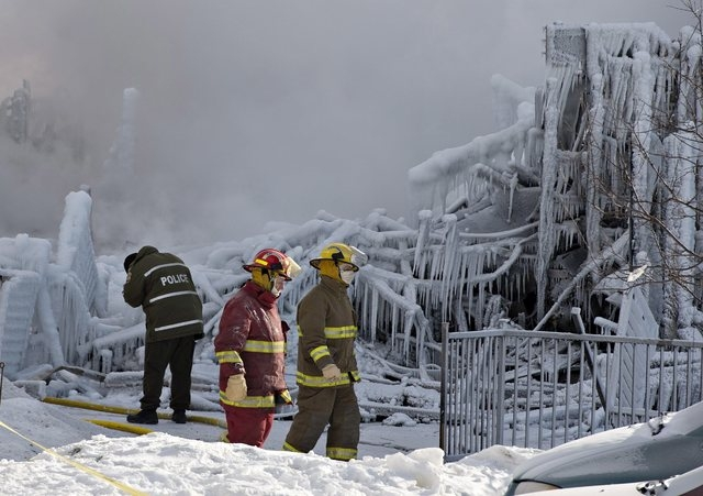 Police and firefighters survey the damage after a fatal fire at a seniors residence in L'Isle-Verte, Quebec, Thursday, Jan. 23, 2014. The fire raged through the seniors' residence, killing at leas ...