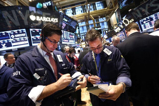 Traders Thomas Donato, left, and Ronald Madarasz work on the floor of the New York Stock Exchange Friday, Jan. 24, 2014.  (AP Photo/Jason DeCrow)