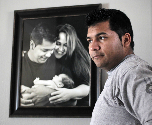 FILE - In this Friday, Jan. 3, 2014 file photo, Erick Munoz stands with an undated copy of a photograph of himself, left, with wife Marlise and their son Mateo, in Haltom City, Texas. Munozs attor ...