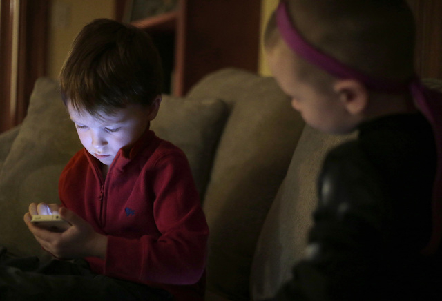 Jameson Young, 4, left, plays with a smart phone as his brother Nolan, 3, looks on at their home in Boston on Monday. (AP Photo/Steven Senne)