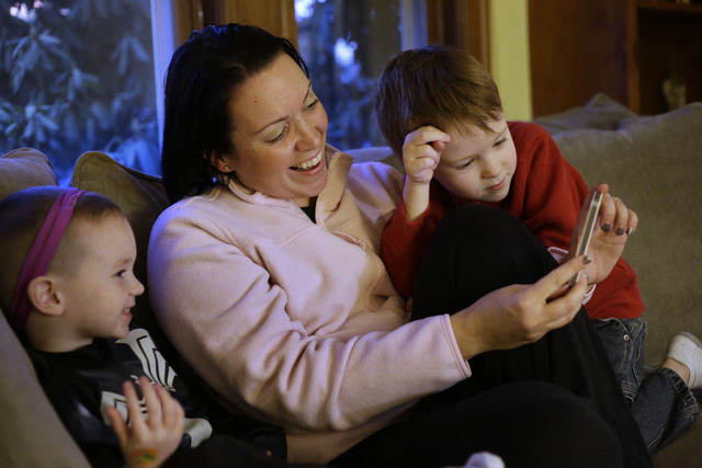 Julie Young, a Boston-based behavioral analyst, sits with her sons Nolan, 3, left, and Jameson, 4, right, while looking at a smart phone at their home in Boston on Monday. Child development expert ...