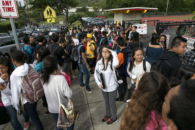 Students look for their parents after they were released from Roosevelt High School on Tuesday after a school shooting on campus in Honolulu. A police officer shot a 17-year-old runaway in the wri ...