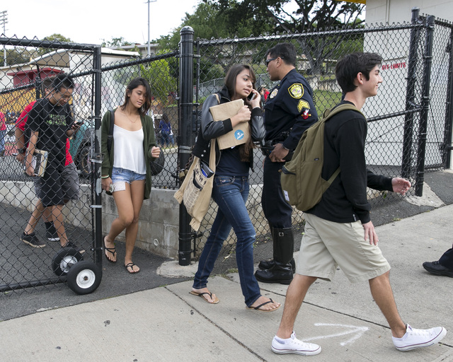 Students leave school at Roosevelt High School after a school shooting on campus on Tuesday in Honolulu. A police officer shot a 17-year-old runaway in the wrist at the high school after the teen  ...