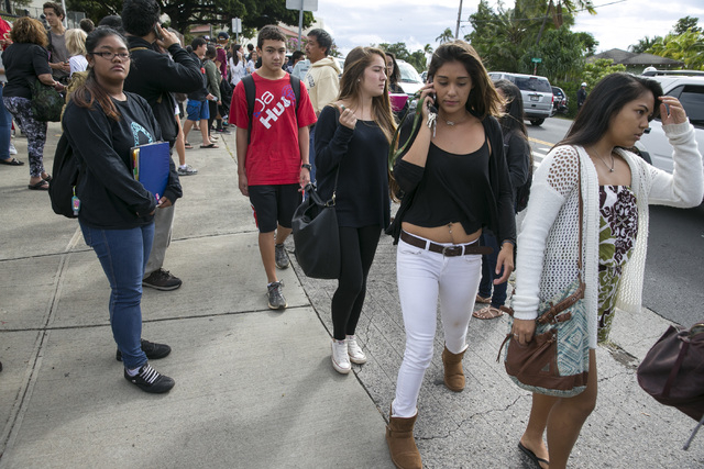 Students leave Roosevelt High School after a school shooting on campus Tuesday in Honolulu. A 17-year-old student was shot by police in a counselor's office after he pulled a knife and cut one of  ...
