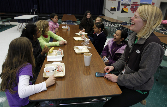 Art teacher Leigh Walker entertains students over breakfast at Oak Mountain Intermediate school on Wednesday in Indian Springs, Ala. About 80 children and 20 adults spent the night at the school d ...
