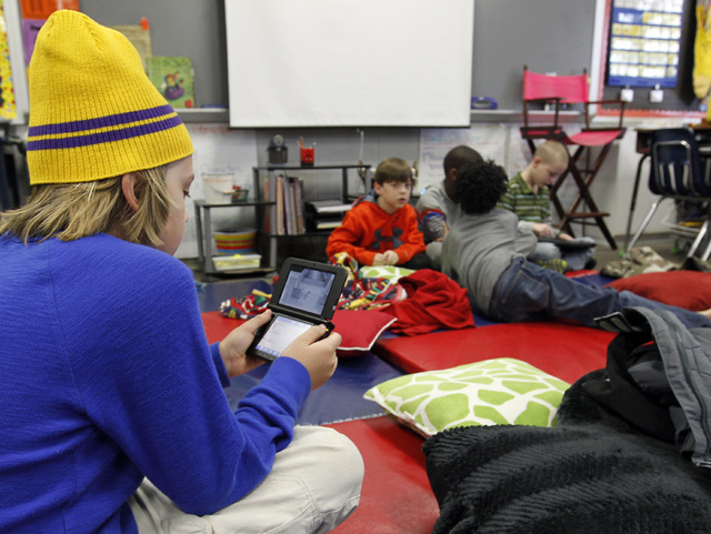 Gavin Chambers plays an electronic game at Oak Mountain Intermediate School on Wednesday in Indian Springs, Ala. About 80 children  and 20 adults spent the night at the school due to a winter stor ...