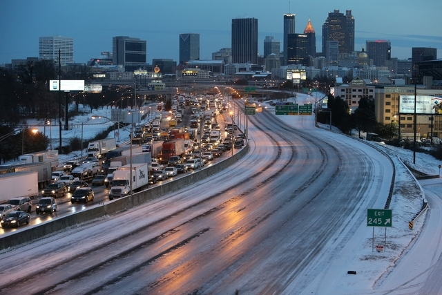 Traffic is at a standstill on the southbound lanes as the northbound side is a empty sheet of ice in Atlanta early Wednesday. After a rare snowstorm stopped Atlanta-area commuters in their tracks, ...