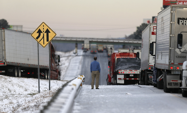 A man stands on the frozen roadway as he waits for traffic to clear along Interstate 75 Wednesday in Macon, Ga. A winter storm dumped snow and covered parts of the state with ice. Gov. Nathan Deal ...