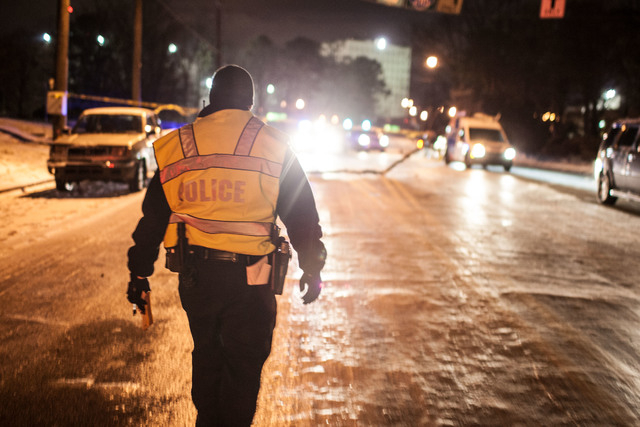 Officer Delaney walks toward stopped traffic on Johnson Ferry Road early Wednesday in Sandy Springs, Ga. Around Atlanta, nearly all public entities and most businesses were shut down early Wednesd ...