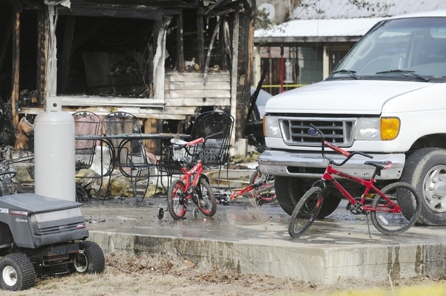 Children's bicycles sit in front of remains of home after an early morning fire Thursday near Greenville, Ky. (AP Photo/The Gleaner, Mike Lawrence)