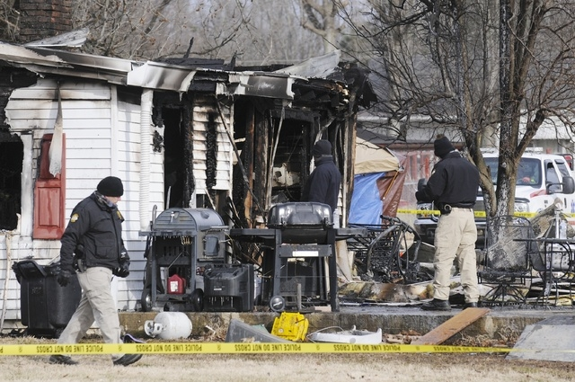 Kentucky State Police fire investigators at the scene of an early morning blaze Thursday at a home near Greenville, Ky. A mother and eight of her children were killed. (AP Photo/The Gleaner, Mike  ...
