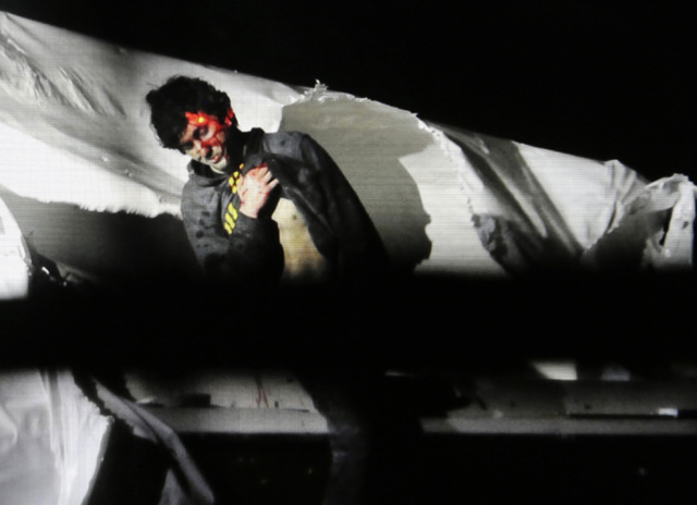 Boston Marathon bombing suspect Dzhokhar Tsarnaev, bloody and disheveled with the red dot of a sniper's rifle laser sight on his head, emerges from a boat at the time of his capture by law enforce ...