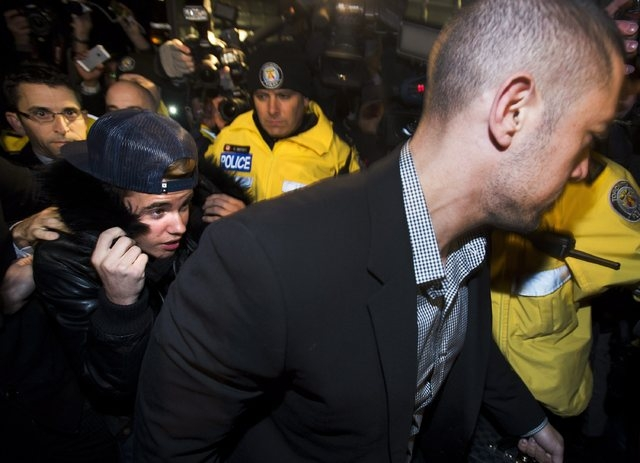 Canadian musician Justin Bieber is swarmed by media and police officers as he turns himself into city police for an expected assault charge, in Toronto, on Wednesday, Jan. 29, 2014. A police offic ...