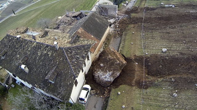 In this photo provided by Tareom.com Thursday, Jan. 30, 2014, and taken on Jan. 23, 2014, a huge boulder is seen after it stopped next to a farm house, while a second giant boulder, which detached ...