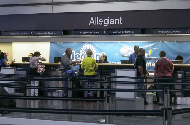 Passengers line up at the Allegiant Air ticketing counter at McCarran International Airport in Las Vegas, Friday, Sept. 20, 2013. Allegiant cancelled and delayed flights leaving McCarran as they c ...