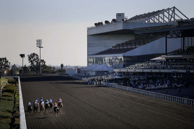 Jockeys and horses race at Betfair Hollywood Park on Saturday, Dec. 14, 2013, in Inglewood, Calif. After 75 years of thoroughbred racing, Betfair Hollywood Park is closed for good. The 260-acre tr ...