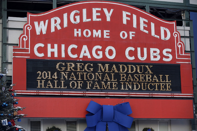 A sign at Wrigley Field in Chicago notes the election of former Chicago Cubs pitcher Greg Maddux to baseball's Hall of Fame on Wednesday. Maddux, Frank Thomas and Tom Glavine were elected to baseb ...