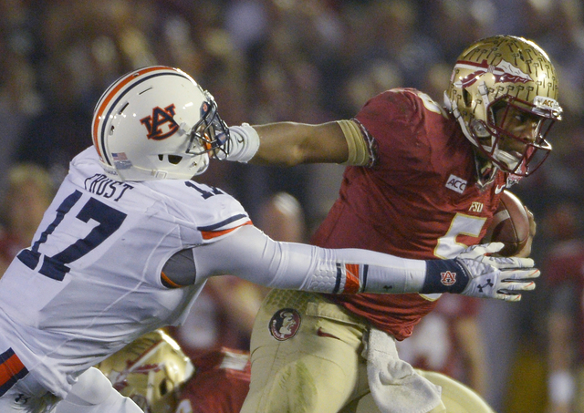 Florida State's Jameis Winston runs past Auburn's Kris Frost during the first half of the NCAA BCS National Championship college football game Monday, Jan. 6, 2014, in Pasadena, Calif. (AP Photo/M ...