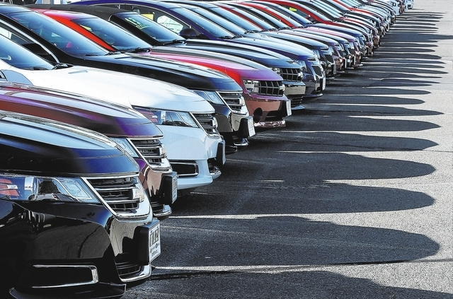 In this Wednesday, Sept. 18, 2013 photo Chevrolet passenger cars form a row on a dealer's lot in Needham, Mass. (AP Photo/Steven Senne)